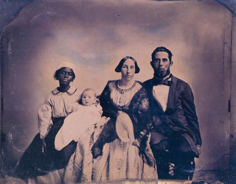 Shows female nursemaid holding white baby. The individuals are not identified, but the place is the town of New Market, in the Shenandoah Valley of Virginia.