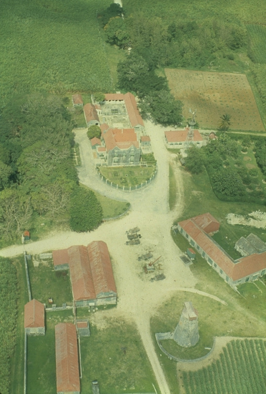 Aerial photo taken by Frederick Lange in 1971-72, shows the plantation house in the center, with the site of the former slave village in the sugar cane field in the upper left; also stables and other out buildings and base of the disused windmill in the lower right. Drax Hall plantation dates from the late 17th century and as of 2002 was still owned by the Drax family in England.