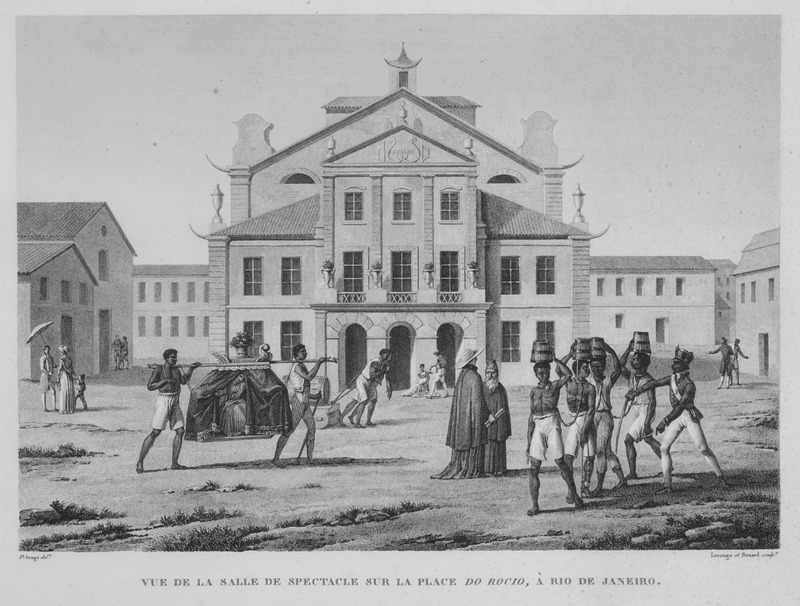 """""""View of the Salle de Spectacle at the Place du Rocio, in Rio de Janeiro"""" (caption translation). In the background was the theatre, Salle de Spectacle, with miscellaneous urban scenes in the foreground of a plaza, Brazil. Two enslaved people carry a woman in a palanquin or covered litter, while a group of enslaved convicts carry water buckets on their heads, linked by chains around their necks. A uniformed guard with a sword is on the right. This engraving, by Lerouge and Bernard, but based on a drawing by Jacques Arago, was published in an elaborate Atlas of 112 plates, some in color, based on drawings made by various artists during a French geographical expedition in the early nineteenth century. The expedition visited Rio in in Dec. 1817-Feb. 1818. The Atlas accompanies a multi-volume account of the expedition, and is sometimes cataloged under the authorship of Ministere de la Marine et des Colonies, rather than Freycinet, the commander of the expedition. Louis Claude de Saulces de Freycinet (1779–1841) was a French navigator, who circumnavigated the earth, and in 1811, published the first map to show a full outline of the coastline of Australia."""