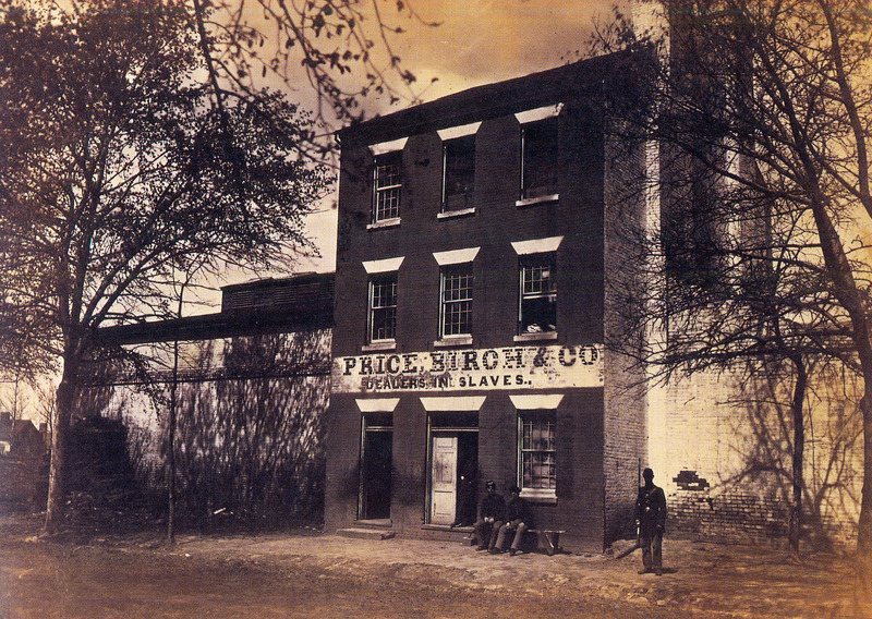 This photograph shows the front of Price, Birch & Co, Dealers in Slaves with unidentified African Americans, in Union army uniforms, in the foreground. Price, Birch, & Co. was a well-known firm that kept slaves in pens or cells before they were sold to the Lower South. Dugan does not specify the location of the photograph, but the original is in the National Archives, Washington, D.C. For a companion photo, see image NW0246 on this website.