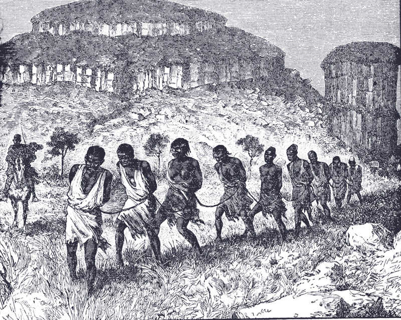 "The image title is misleading and incorrect because the slave traders are not Portuguese. The image shows a line of men and women lashed together by ropes, guarded by a horse-mounted slave trader, who was likely a Mande speaker or Soninke (Sarakole) or Dioula (Jula). The illustration in Buel's volume was, in fact, taken from Joseph Simon Gallièni, Mission d'exploration du Haut-Niger: Voyage au Soudan Francais (Paris, 1885), p. 525. Therein, the caption reads Le Mana-Oulè et caravan d'esclaves, or ""The Mana-Oulè and Caravan of Slaves."" Mana-Oulè is the rocky geological formation shown in the background located in the Senegambia region."