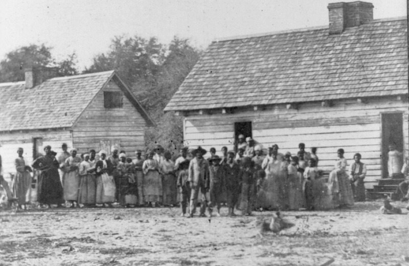 Photographic print showing men, women, and children standing in front of barrack-like cabins at Smith's plantation.