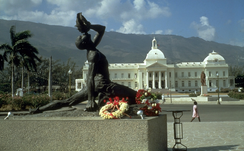 Le Negre Marron (The Black Maroon; in creole, Neg Mawon), often translated in English as the Unknown Slave, although Fugitive or Rebel Slave would probably be more accurate in the context of Haitian history. Located on the boulevard Champ de Mars with Haiti's presidential palace in background. The Negre Marron is shown with left leg extended (broken chain on his ankle); a machete (partially hidden by flower wreaths) is in his right hand, and his left hand holds a conch shell to his lips. The conch shell was often used as a trumpet to assemble people. Created by the Haitian sculptor/architect, Albert Mangones (1917-2002) in 1968 or 1969, the statue was commissioned by the government of president Francois Duvalier to commemorate the slaves who revolted against France. (Thanks to several respondants on Caribbean List Serve, including Lorraine Mangones, the sculptor's daughter, for information on the statue). The wreaths shown in this photograph were laid by the South Korean Ambassador who had presented his credentials not long before the photograph was taken in April 1970. Le Negre Marron survived the horrible earthquake of 12 January 2010, but the presidential palace was destroyed (Thanks to Robert Fatton for this information).
